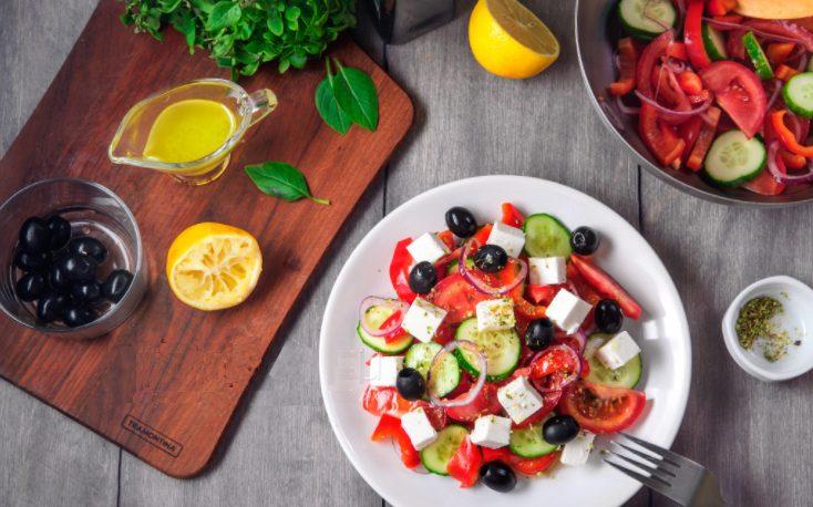 Narezannyye ovoshchi vykladyvayem na tarelki, sverkhu raskladyvayem olivki i narezannuyu kubikami brynzu